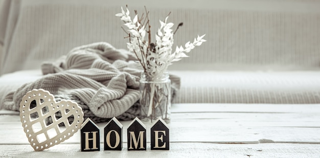 Samenstelling in hygge-stijl met het houten woord home, decordetails en een gebreid element