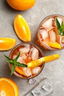 Samenstelling met aperol spritz cocktail op grijze achtergrond