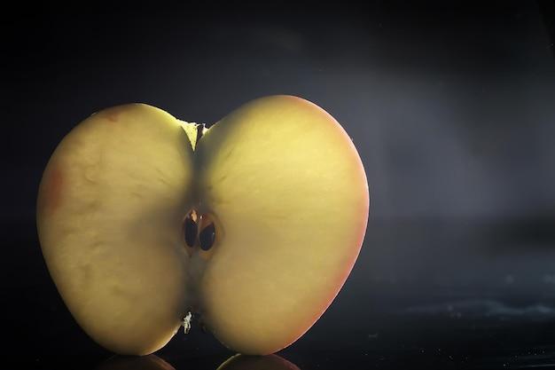 Samenstelling met appelschijfjes op een zwarte achtergrond. een schijfje appel met achtergrondverlichting op een zwarte achtergrond met waterdruppels. sappige appel op een tafel.