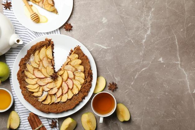 Samenstelling met appeltaart en ingrediënten op grijze achtergrond, bovenaanzicht