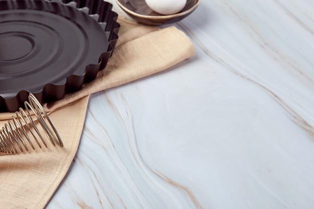 Samenstelling met bakgerei en kookingrediënten voor taarten, koekjes, deeg en gebak op marmer.