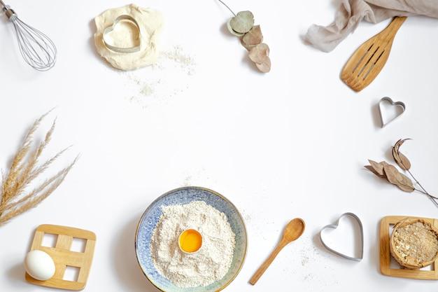 Samenstelling met bakselingrediënten en keukenaccessoires op een witte tafel.