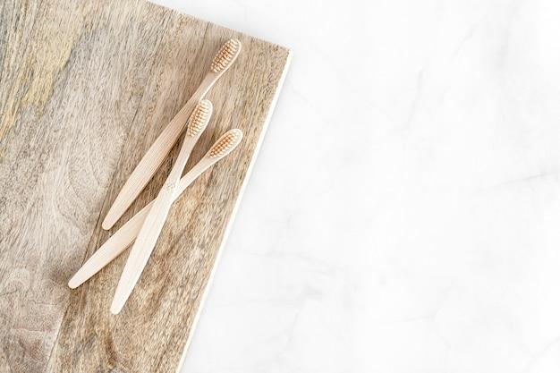 Samenstelling met biologisch afbreekbare bamboetandenborstels op marmeren achtergrond.