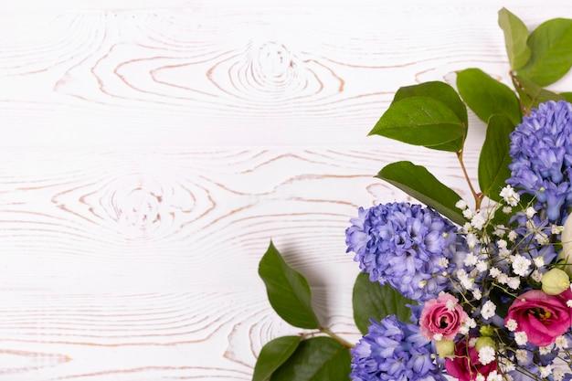 Samenstelling met blauwe en magenta rozen op een witte houten tafel