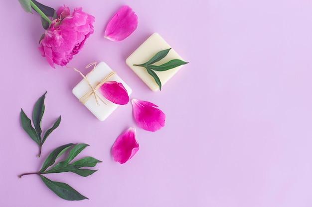 Samenstelling met bloemen, bloemblaadjes van pioenroos, natuurlijke biologische zeep. schoonheid, huidverzorging concept. plat lag, bovenaanzicht
