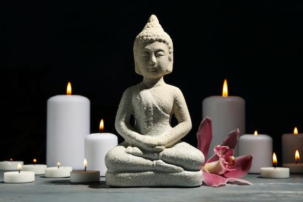 Samenstelling met boeddha en kaarsen op houten tafel. zen concept