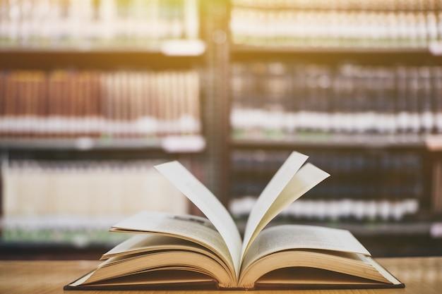 Samenstelling met boeken, op houten dek tafel en boekenplank achtergrond.
