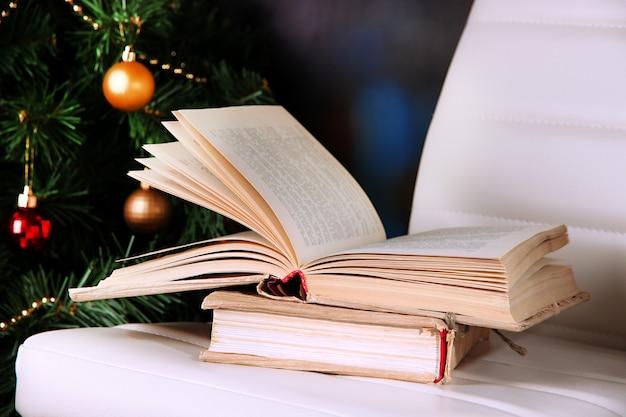 Samenstelling met boeken over stoel op kerstboomachtergrond