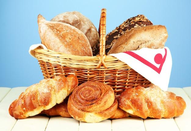 Samenstelling met brood en broodjes, in rieten mand op houten tafel, op kleur achtergrond