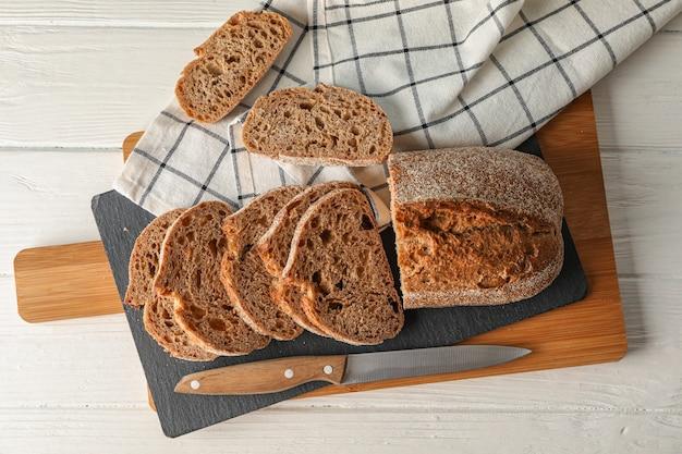 Samenstelling met brood, mes, keuken handdoek en snijplank op witte houten ruimte, bovenaanzicht en ruimte voor tekst