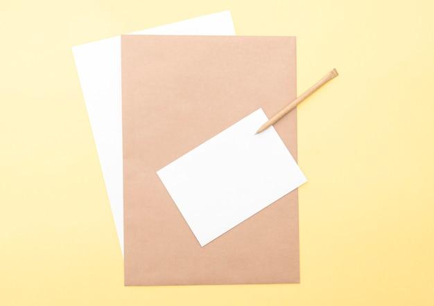 Samenstelling met bruine en witte blanco vellen, pen op gele achtergrond, lay-out met ruimte voor tekst, bovenaanzicht
