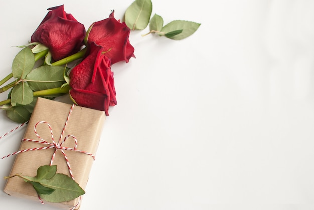 Samenstelling met cadeau en boeket rode rozen op witte achtergrond