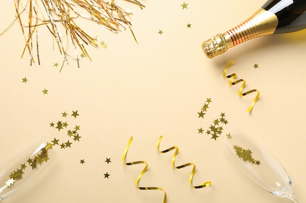 Samenstelling met champagnefles, glazen en glitter op beige, kopie ruimte