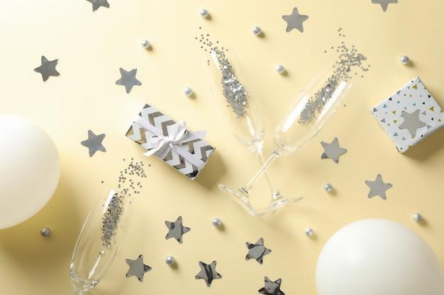 Samenstelling met champagneglazen, geschenken en glitter op beige, bovenaanzicht