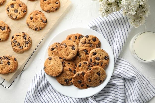 Samenstelling met chip cookies, bloemen en melk op witte tafel
