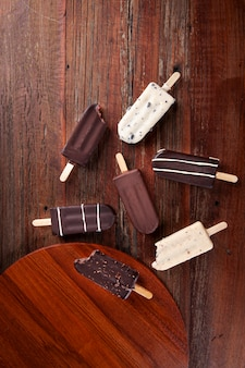 Samenstelling met chocolade ijslollys op houten achtergrond. bovenaanzicht