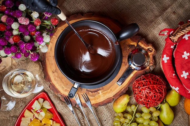 Samenstelling met chocoladefondue in pot en ruimte voor tekst op marmeren achtergrond