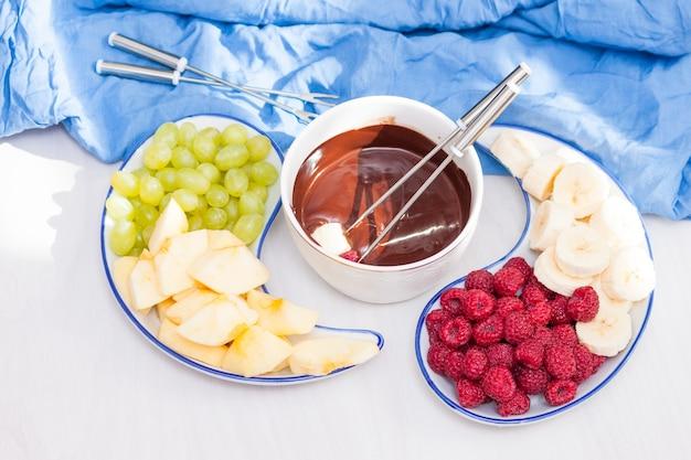 Samenstelling met chocoladefondue in pot, fruit, bessen op witte tafel. bovenaanzicht