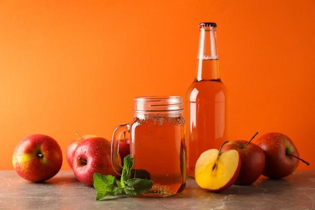 Samenstelling met cider en appels op grijze tafel