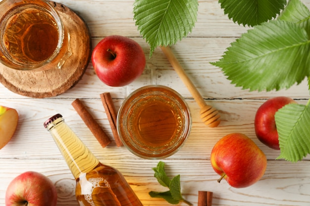 Samenstelling met cider, kaneel en appels op houten tafel