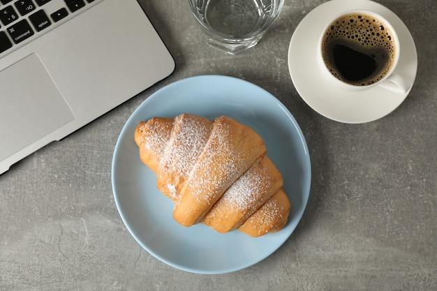 Samenstelling met croissant en computer op grijze achtergrond, bovenaanzicht