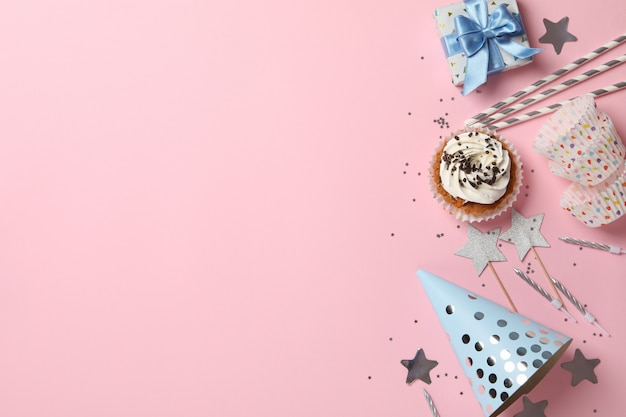 Samenstelling met cupcake en verjaardag accessoires op roze achtergrond, ruimte voor tekst