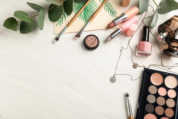 Samenstelling met decoratieve cosmetica en accessoires op witte houten achtergrond