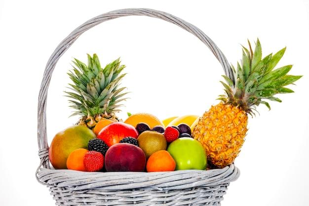 Samenstelling met diverse vruchten in rieten die mand op wit wordt geïsoleerd