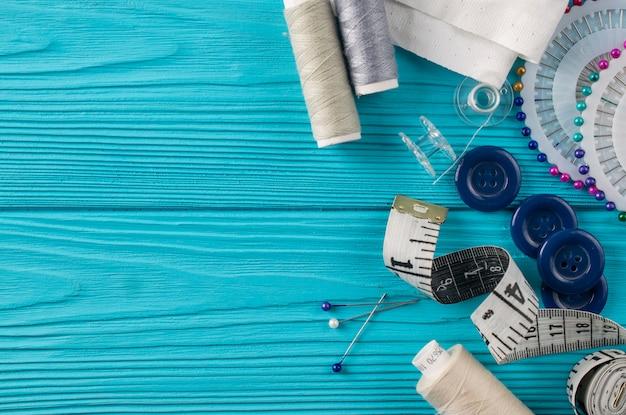 Samenstelling met draden en naaiende accessoires op blauwe achtergrond
