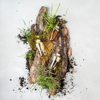 Samenstelling met drie glazen flessen lichaamsverzorgings biologische cosmetica met olie frangipani, sandelhout, patchouli