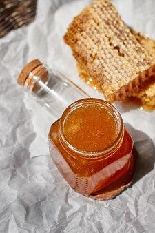 Samenstelling met een glazen pot met honing en honingraat op een rieten tafel met calqueerpapier