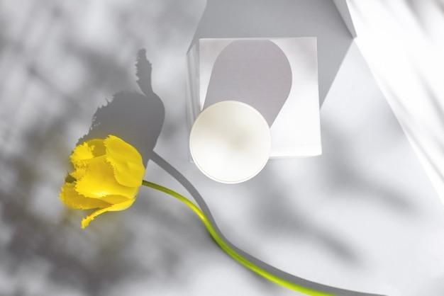 Samenstelling met een potje room, kubus, gele tulp en schaduwen. concept rond het thema jeugd en schoonheid.