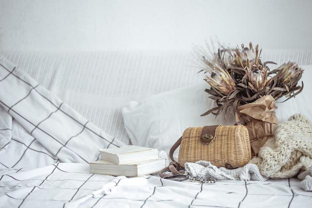 Samenstelling met een rieten handtas, boeken en een boeket gedroogde bloemen kopie ruimte