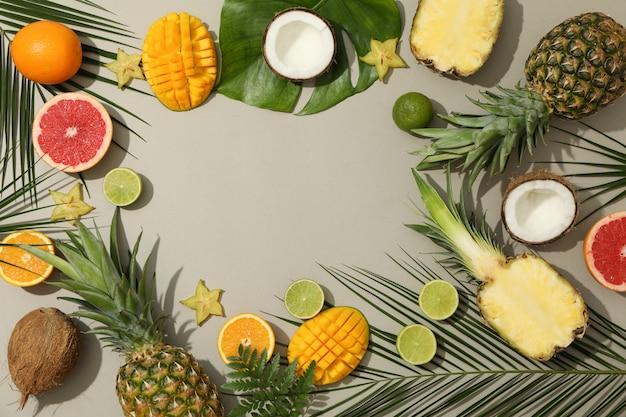 Samenstelling met exotische vruchten en palmbladeren op grijze achtergrond, ruimte voor tekst