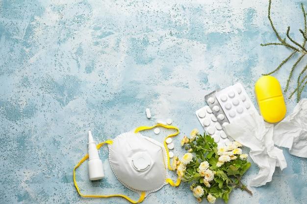 Samenstelling met fles druppels, bloemen en gasmasker op blauw beton, bovenaanzicht
