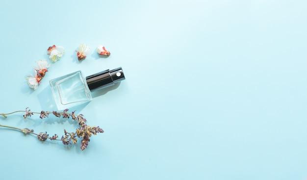 Samenstelling met fles parfum en bloeiende bloem. aromatherapie concept met bovenaanzicht en kopie ruimte flat lay.