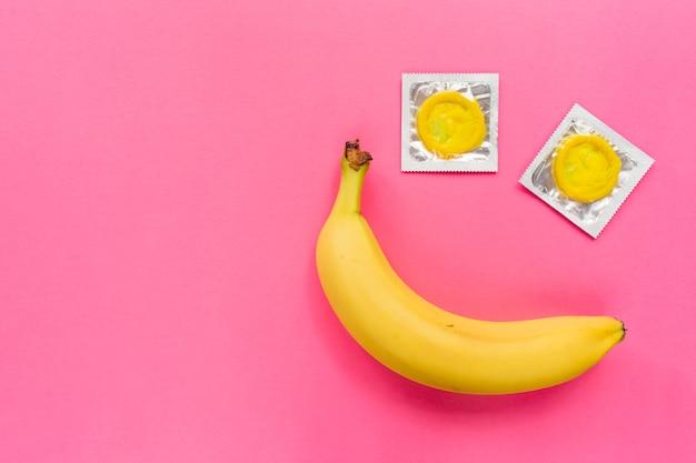 Samenstelling met gele condooms en banaan op roze achtergrond. veilig vrijen en anticonceptieconcept. plat lag, bovenaanzicht, kopieer ruimte.