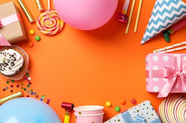 Samenstelling met geschenkdozen en b-day accessoires op oranje achtergrond, ruimte voor tekst