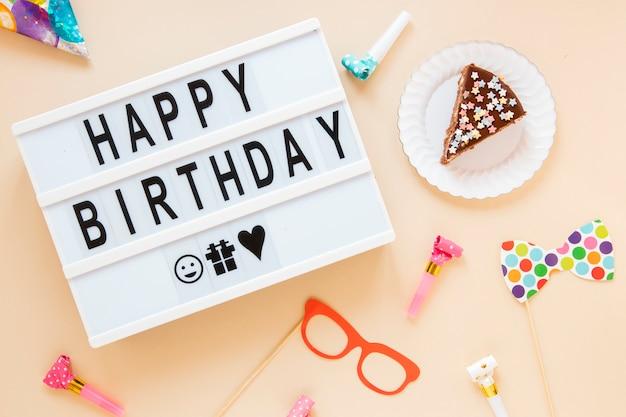 Samenstelling met gesneden cake en verjaardag belettering