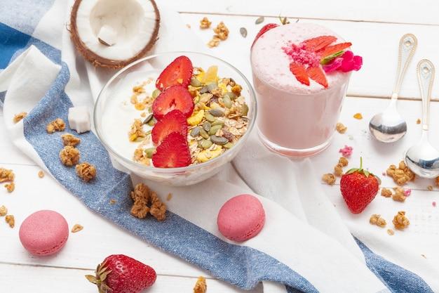 Samenstelling met gezond voedsel. aardbeien en yoghurtontbijt op lijst
