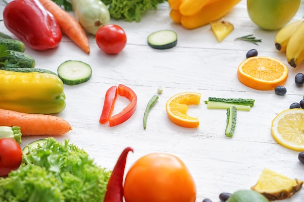 Samenstelling met gezonde producten en woord dieet op lichte houten oppervlakte