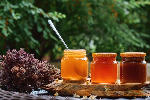Samenstelling met glazen potten honing liggend op een rieten tafel