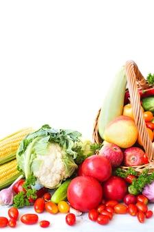 Samenstelling met groenten en fruit in rieten die mand op wit wordt geïsoleerd. gezond eten.