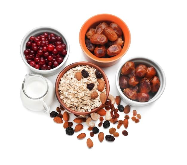 Samenstelling met havermoutvlokken, droog fruit en melk op een witte ondergrond