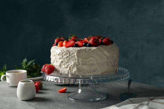Samenstelling met heerlijke berry cream cake op grijze tafel