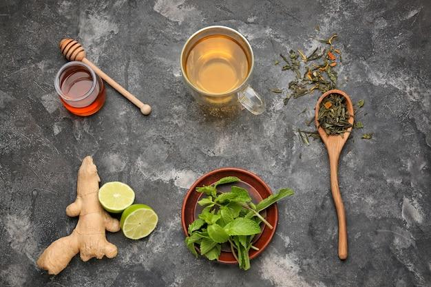 Samenstelling met hete thee en ingrediënten op grungetafel