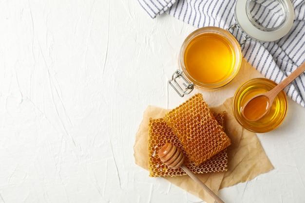 Samenstelling met honingraten en honing op witte achtergrond
