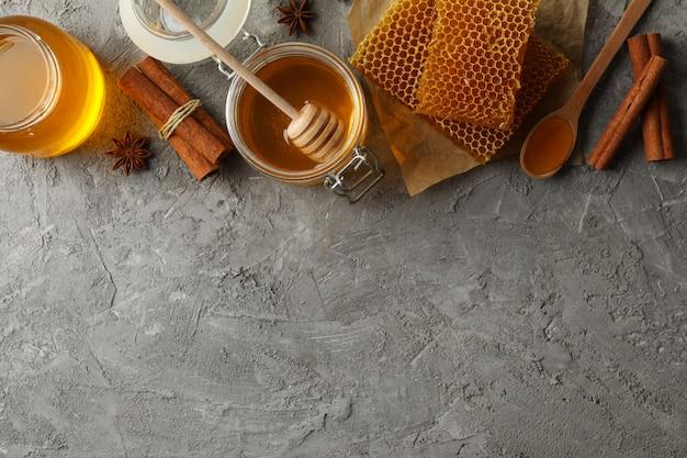 Samenstelling met honingraten, honing en kaneel op grijze achtergrond