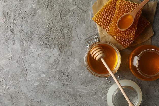 Samenstelling met honingraten, honing en potten op grijze achtergrond