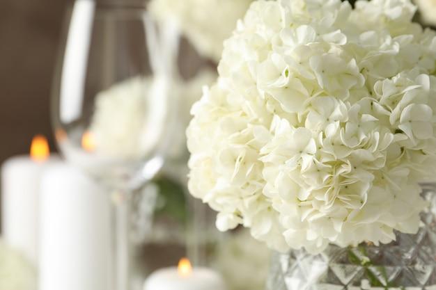 Samenstelling met hortensia bloemen en kaarsen tegen bruine ruimte. romantische avond